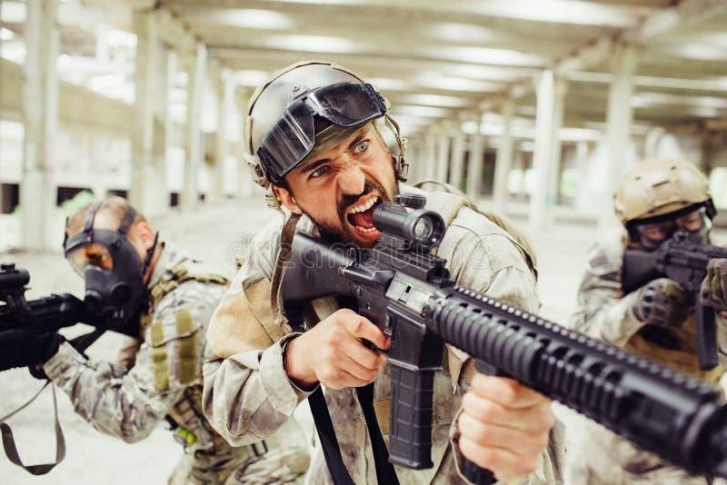 O soldado farpado está gritando e está gritando Tem o rifle longo em suas mãos O indivíduo está estando na frente de seus combate imagem de stock
