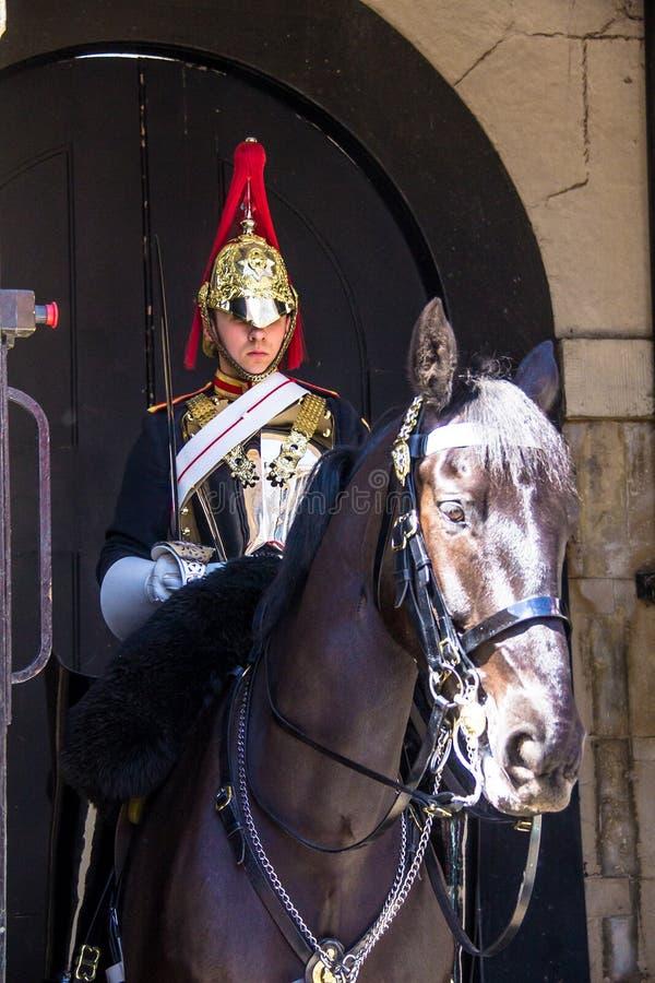 O soldado montado da cavalaria do agregado familiar no dever em protetores de cavalo aproxima o museu da cavalaria do agregado fa fotografia de stock royalty free
