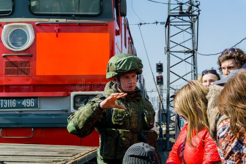 O soldado mostra a civis a exposição móvel dos troféus do exército do russo durante a campanha síria foto de stock