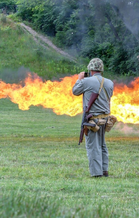 O soldado olha chamas de um atirador de chama fotografia de stock royalty free