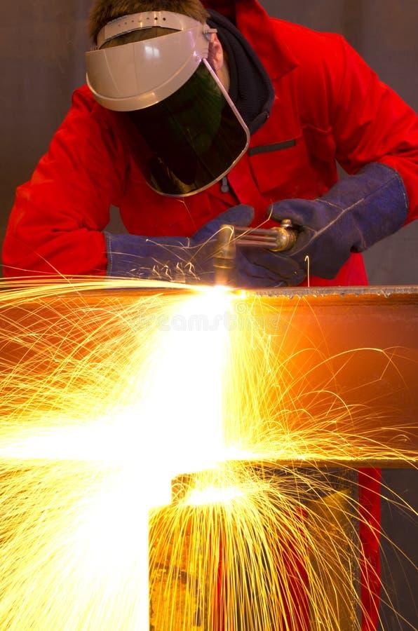 O soldador dobra-se para cortar o feixe do metal com faíscas alaranjadas. imagens de stock royalty free