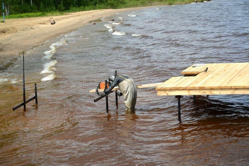 O soldador elétrico funciona na construção da amarração no reservatório de Rybinsk Região de Yaroslavl imagem de stock