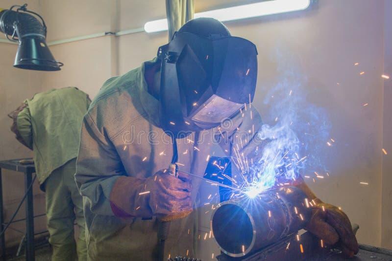 O soldador em luvas amarelas solda duas partes da tubulação de aço usando a soldadura elétrica imagens de stock