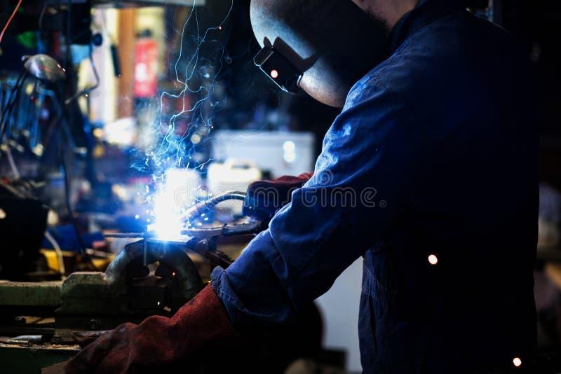 O soldador está soldando na garagem, trabalhador do trabalhador industrial na construção de aço de solda da fábrica foto de stock