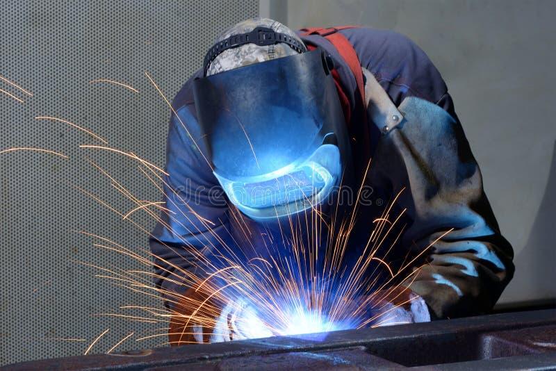 O soldador funciona em uma empresa industrial - produção de comp(s) do aço fotografia de stock