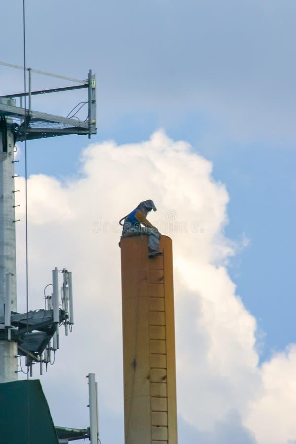 O soldador toma uma ruptura das seções torching da torre de água ao sentar-se no grande tubo de aço imagens de stock