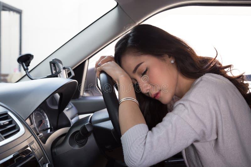 O sono cansado da jovem mulher no carro, trabalho duro causa a saúde pobre, senta adormecido quando o carro estiver em uma luz ve foto de stock royalty free