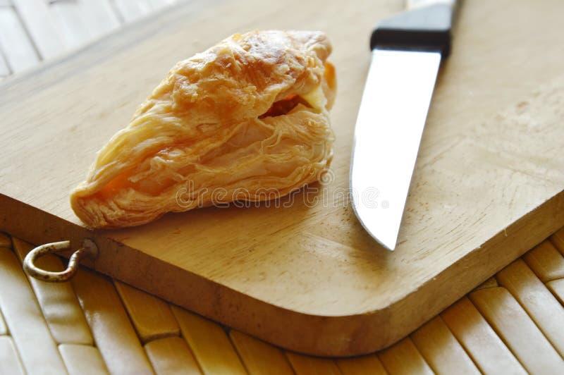 O sopro friável encheu a salsicha de carne de porco e triturou o feijão com a faca no bloco de madeira da costeleta fotos de stock royalty free