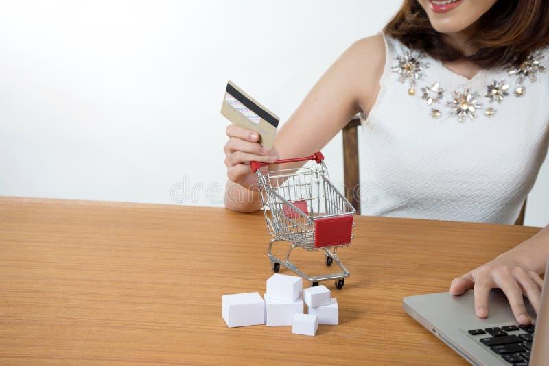 O sorriso asiático do assento da mulher usa seu computador fotografia de stock royalty free