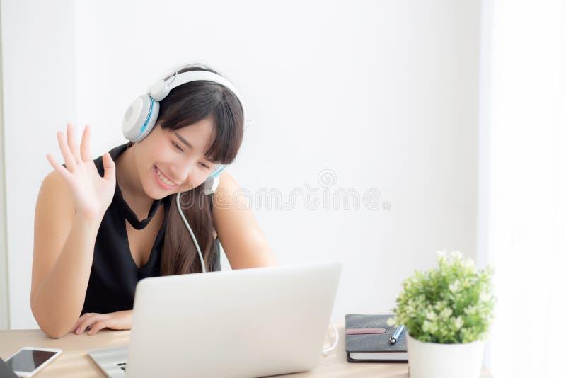 O sorriso asiático novo bonito do fones de ouvido do desgaste de mulher diz que olá! usando o vídeo do bate-papo chamar o laptop imagem de stock