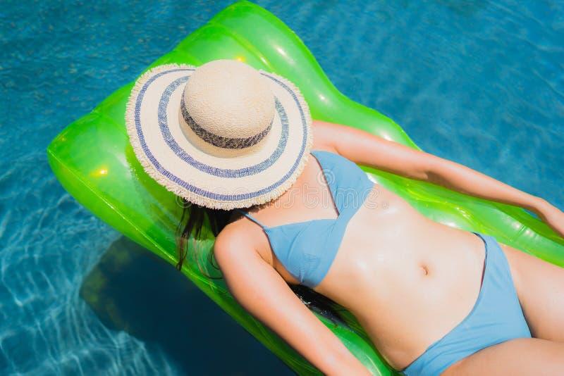 O sorriso asi?tico novo bonito da mulher do retrato feliz relaxa e lazer na piscina imagens de stock royalty free