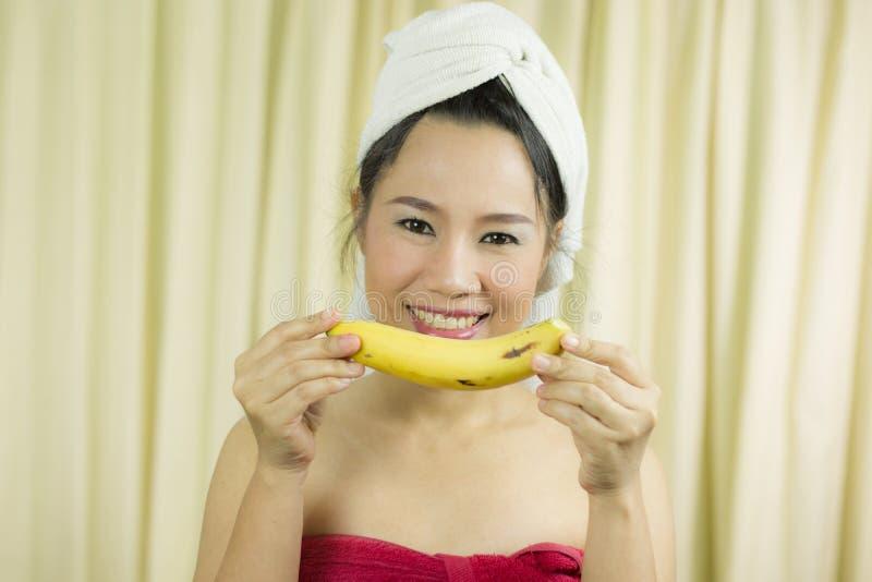 O sorriso ativo da banana da terra arrendada da mulher, triste, engraçado, veste uma saia para cobrir seu peito após o cabelo d fotos de stock