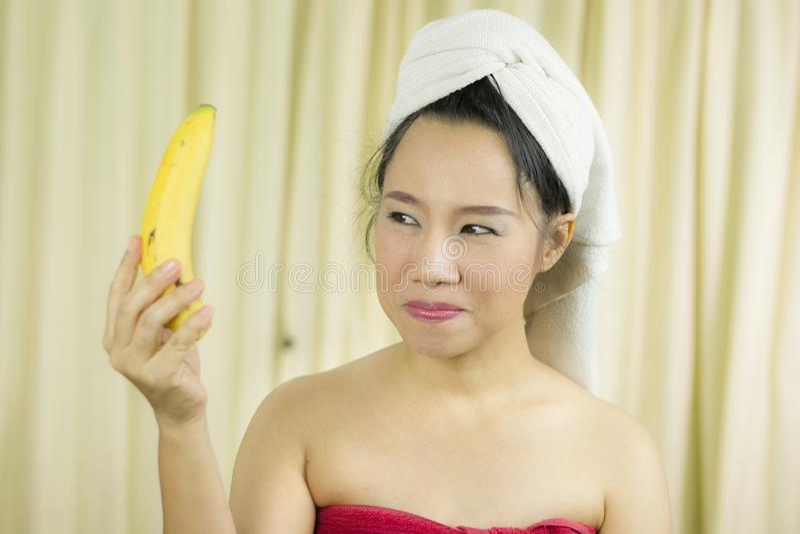 O sorriso ativo da banana da terra arrendada da mulher, triste, engraçado, veste uma saia para cobrir seu peito após o cabelo d fotografia de stock royalty free