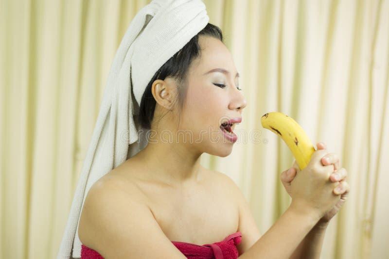 O sorriso ativo da banana da terra arrendada da mulher, triste, engraçado, veste uma saia para cobrir seu peito após o cabelo d foto de stock
