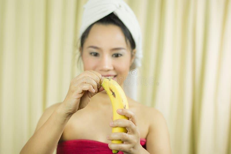O sorriso ativo da banana da terra arrendada da mulher, triste, engraçado, veste uma saia para cobrir seu peito após o cabelo d fotografia de stock