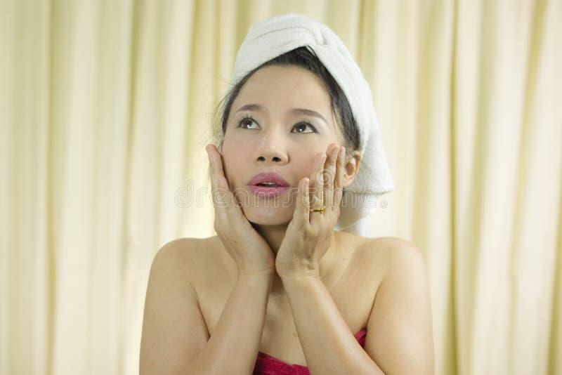 O sorriso ativo da mulher, triste, engraçado, veste uma saia para cobrir seu peito após o cabelo da lavagem, envolvido nas toal fotos de stock royalty free