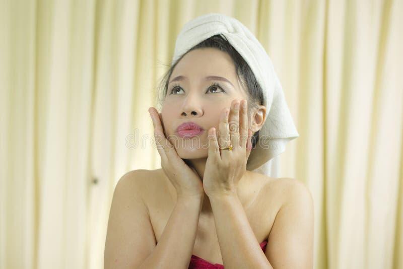 O sorriso ativo da mulher, triste, engraçado, veste uma saia para cobrir seu peito após o cabelo da lavagem, envolvido nas toal fotos de stock