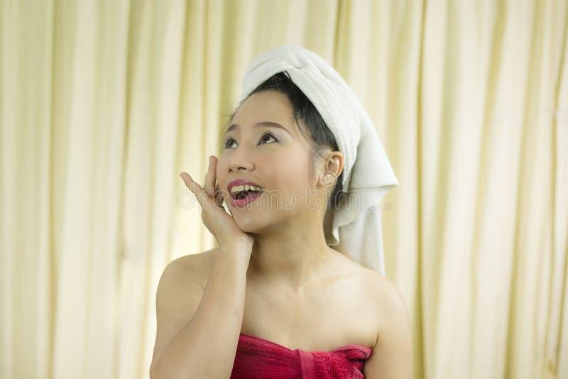 O sorriso ativo da mulher, triste, engraçado, veste uma saia para cobrir seu peito após o cabelo da lavagem, envolvido nas toal imagens de stock royalty free