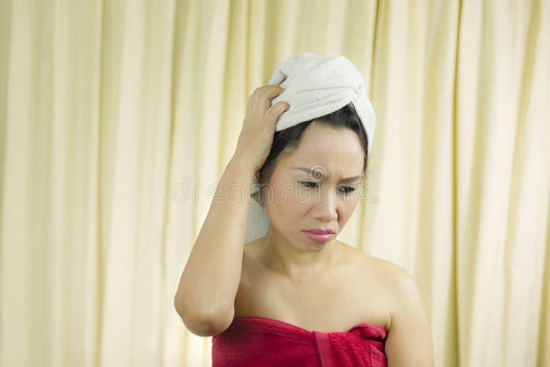 O sorriso ativo da mulher, triste, engraçado, veste uma saia para cobrir seu peito após o cabelo da lavagem, envolvido nas toal imagens de stock