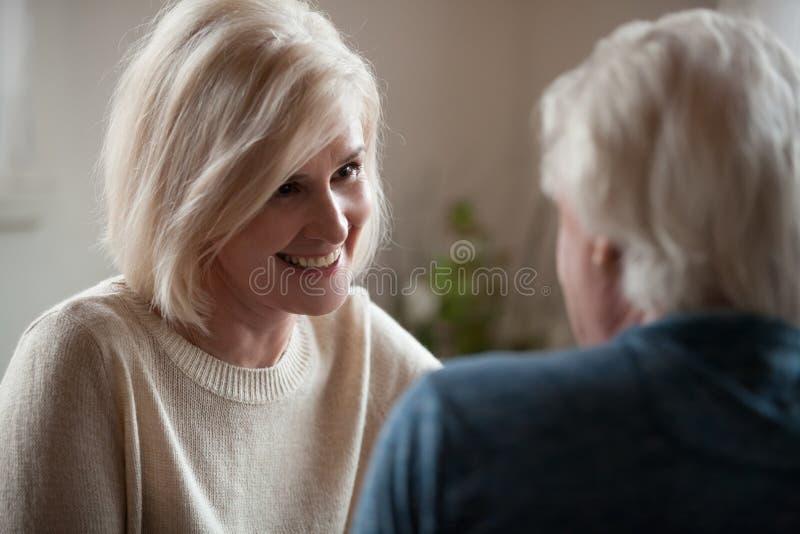 O sorriso atrativo envelheceu a fala fêmea com marido foto de stock