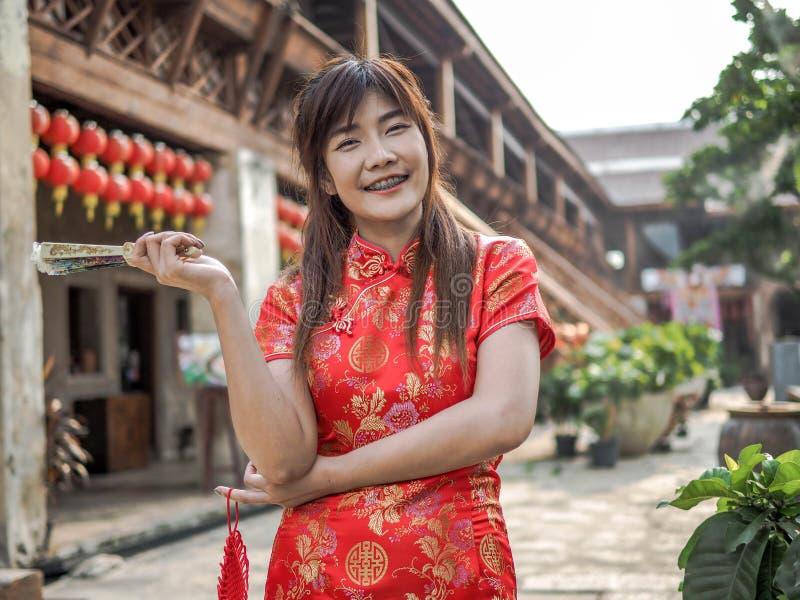 O sorriso bonito da jovem mulher veste o cheongsam profundo - vestido vermelho que guarda um fã que olha a câmera Ano novo chinês fotos de stock royalty free