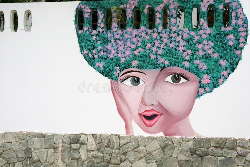 O sorriso bonito e a senhora grande dos olhos dirigem a arte da flor na parede fotos de stock