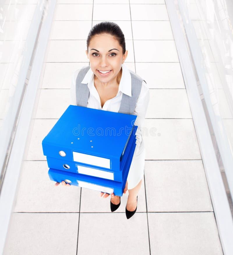 O sorriso da mulher de negócios, guarda o dobrador azul da pilha fotografia de stock