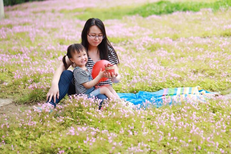 O sorriso e o jogo bonitos pequenos felizes do bebê balloon com mãe, a mamã diz a história a sua filha em uma família feliz do pa imagens de stock royalty free