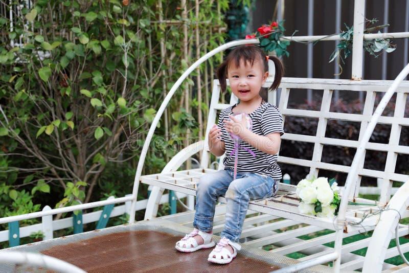 O sorriso e o jogo chineses da criança da menina bonita bonito pequena sentam em uma posse branca dos bancos um pirulito e uma fl fotografia de stock royalty free