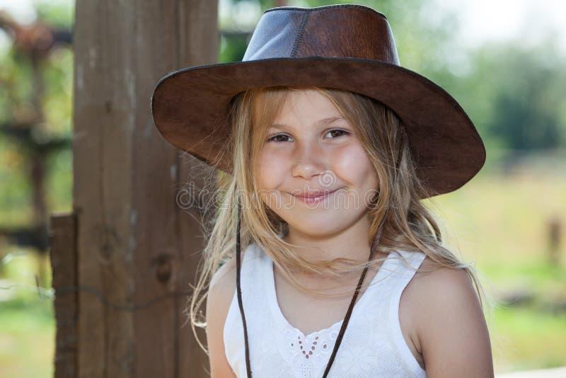 O sorriso e a menina caucasiano feliz no retrato de couro do chapéu de vaqueiro, cabelo louro longo, bronzeiam os olhos imagens de stock