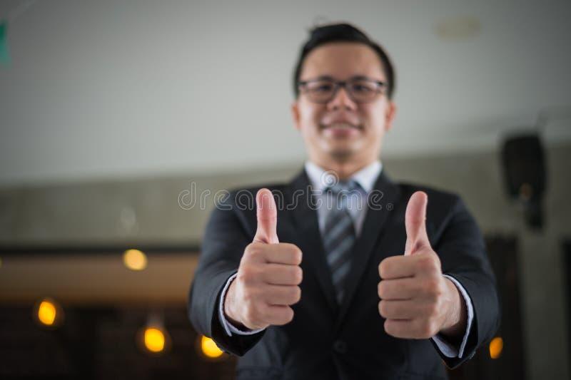 O sorriso e a mostra asiáticos do homem de negócios manuseiam acima dois da mão no escritório, conceito bem sucedido fotos de stock