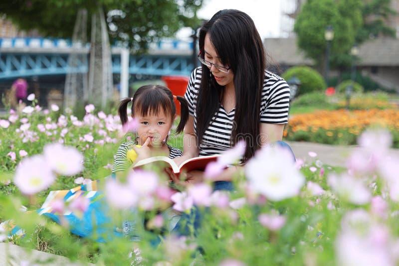 O sorriso e o riso bonitos pequenos felizes do bebê leem o livro com mãe, a mamã diz a história a sua filha em uma família feliz  imagem de stock