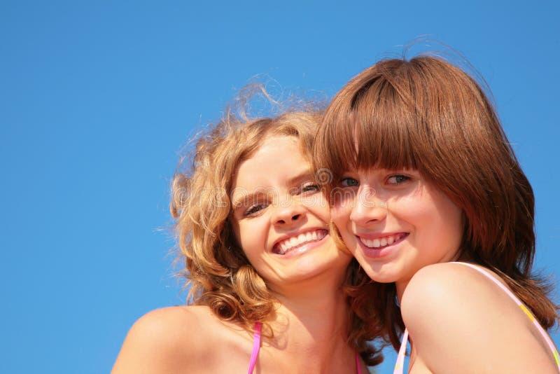 O sorriso enfrenta meninas no céu do verão fotografia de stock