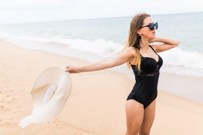 O sorriso entusiasmado feliz da jovem mulher na posse do oceano da praia aumentou as mãos de braços acima, o chapéu e o roupa de  foto de stock royalty free
