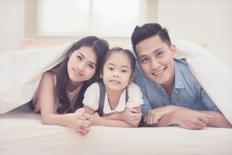 O sorriso feliz da família asiática e relaxa na cama em casa fotografia de stock royalty free