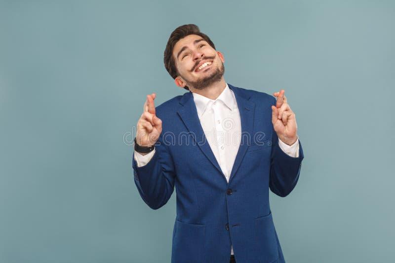 O sorriso toothy do homem de negócio, os dedos cruzados deseja, reza e espera fotos de stock