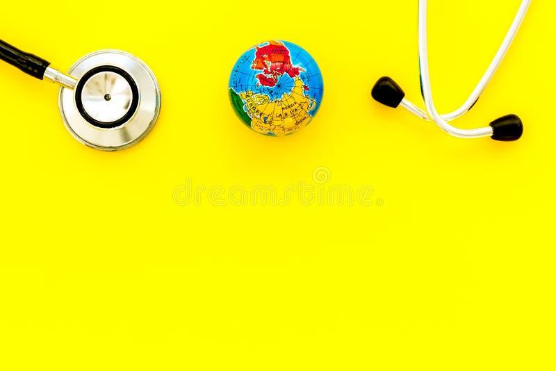 O SOS salvar o conceito do planeta e da ecologia com a terra e o phonendoscope na zombaria amarela da opinião superior do fundo a fotos de stock royalty free