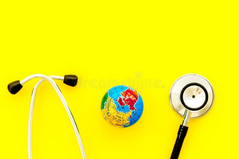 O SOS salvar o conceito do planeta e da ecologia com a terra e o phonendoscope na zombaria amarela da opinião superior do fundo a fotografia de stock