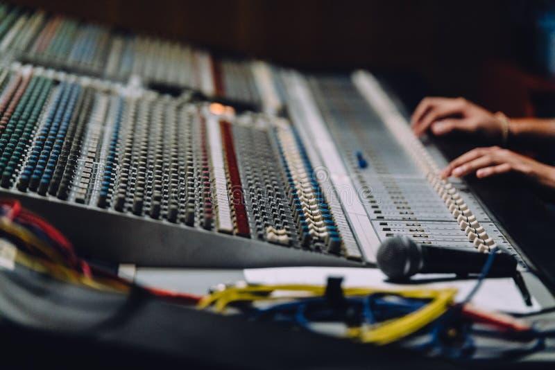 O soundboard próximo das mãos profissionais está misturando sons pelo painel de controle audio do misturador com os botões e os s fotografia de stock