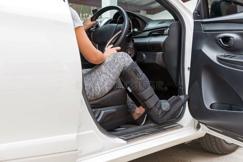 O sportsware vestindo da mulher de Injurred com preto moldou no pé que senta-se no carro branco, conceito do seguro imagens de stock royalty free