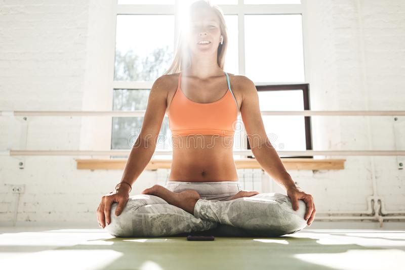 O sportwear da mulher apta que veste os fones de ouvido sem fio que fazem esticando o exercício que senta-se na esteira da ioga n imagem de stock