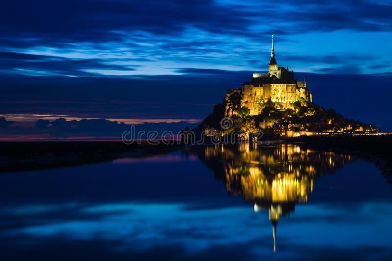 O St. Michel de Mont refletiu no mar no por do sol imagem de stock