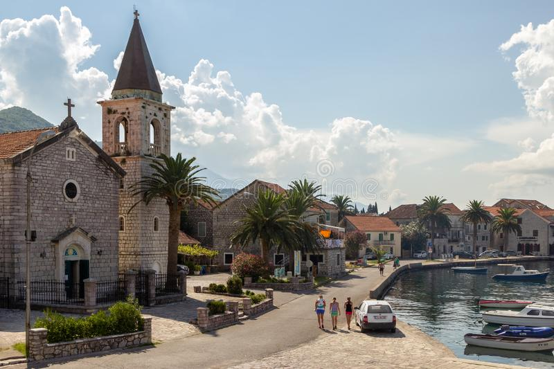 O St Roko Church do católico, casas de pedra antigas nas costas da baía de Boka Kotorska imagem de stock