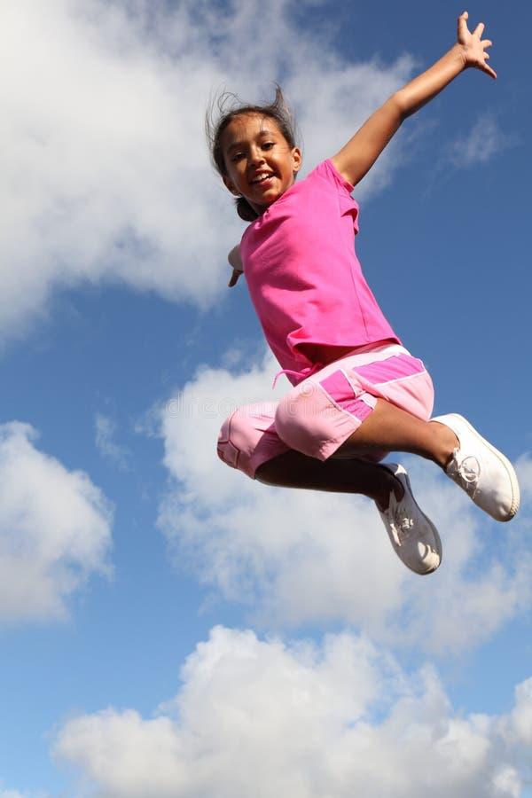 O sucesso mostra em menina excited que pula no ar imagens de stock royalty free