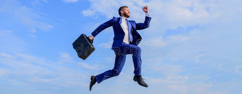 O sucesso no negócio exige esforços sobrenaturais Homem de negócios com o salto da pasta alto no movimento para a frente Homem de fotos de stock royalty free
