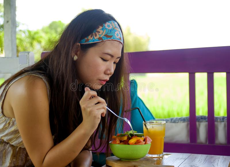 O suco de laranja bebendo novo da mulher coreana asiática bonita e feliz que come a salada saudável na cafetaria do alimento biol fotografia de stock