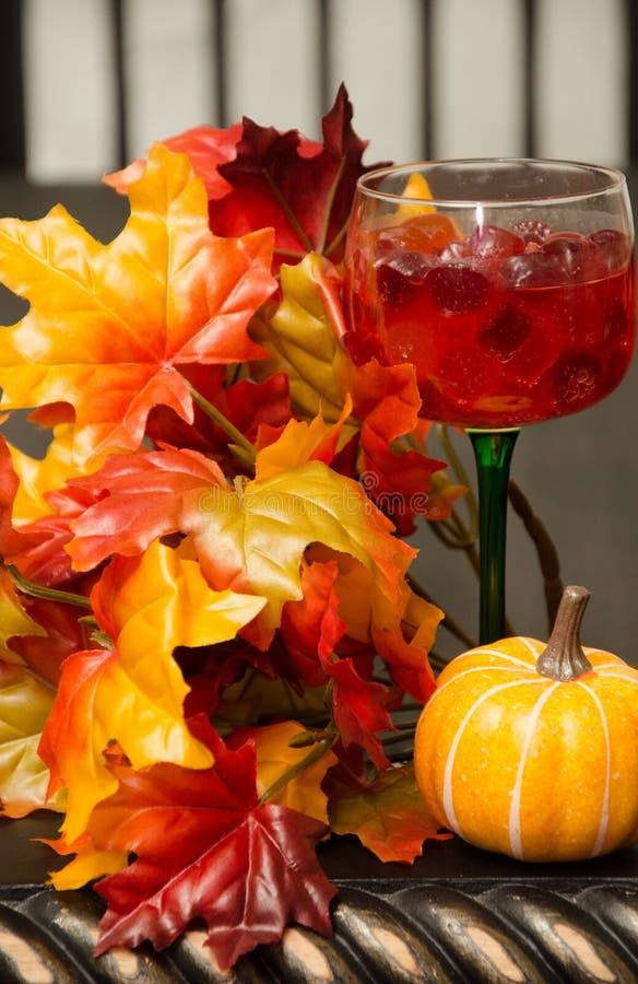 O suco e os doces encheram o vidro de vinho com a folha do outono imagens de stock