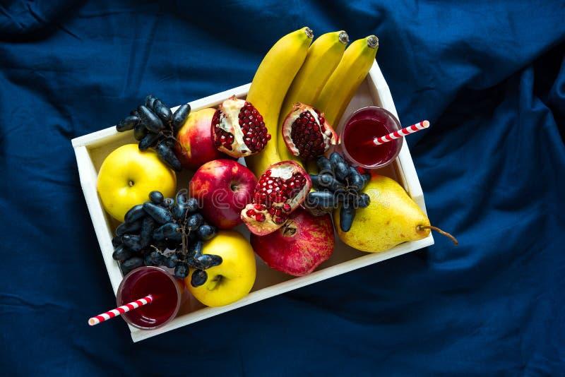 O suco fresco vermelho com maçãs, peras, bananas, uvas e romã frutifica na bandeja de madeira branca no shee azul da cama imagens de stock royalty free