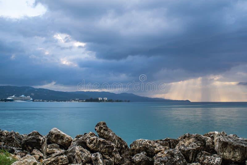 O Sunburst no por do sol em Montego Bay Jamaica com o navio de cruzeiros de Marella Discovery 2 entrou no porto fotos de stock