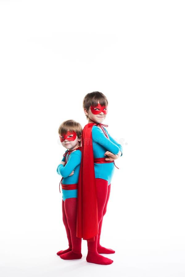 O super-herói de dois meninos com um comprimento completo da máscara e do casaco olha a câmera foto de stock royalty free